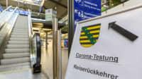 Schild mit Aufforderung zum Coronatest für Reiserückkehrer im Flughafen Leipzig