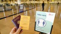 Hand hält beim Check-in französischen Pass und Impfausweis in der Hand
