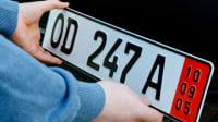 Zwei Hände montieren ein deutsches Ausfuhrkennzeichen an ein schwarzes Auto