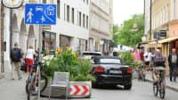 Eine Spielstraße mit Autos, Radfahrern und Fußgängern