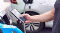 Mann nutzt eine App, um sein Elektroauto zu laden