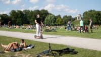 Ein junger Mann fährt auf einem E-Scooter im englischen Garten in München