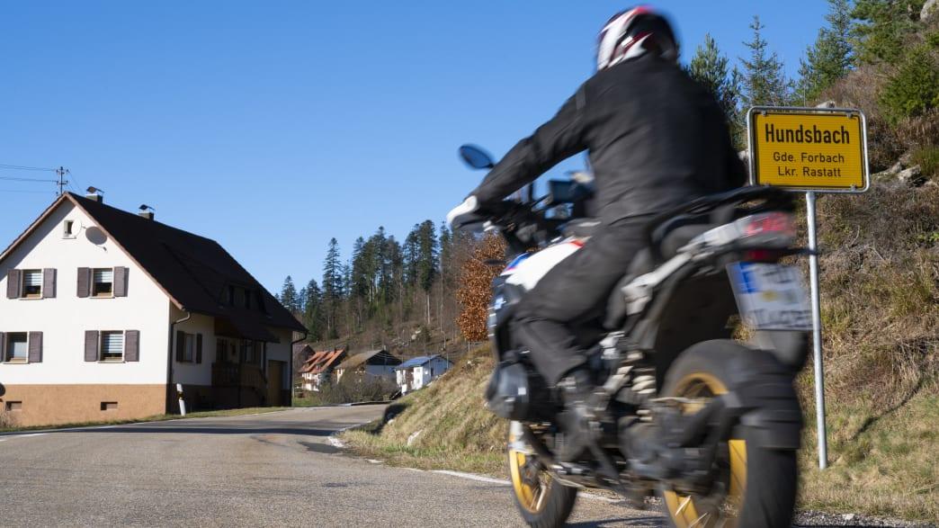 Motorradfährer fährt auf Straße am Ortseingang zu Hundsbach