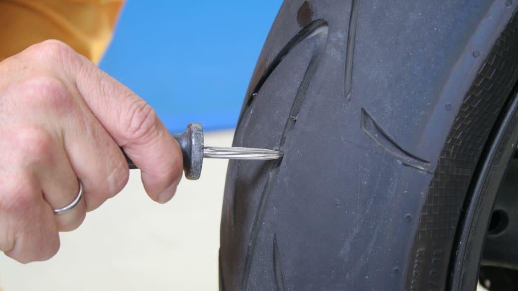 Loch an einem Motorradreifen wird aufgerieben