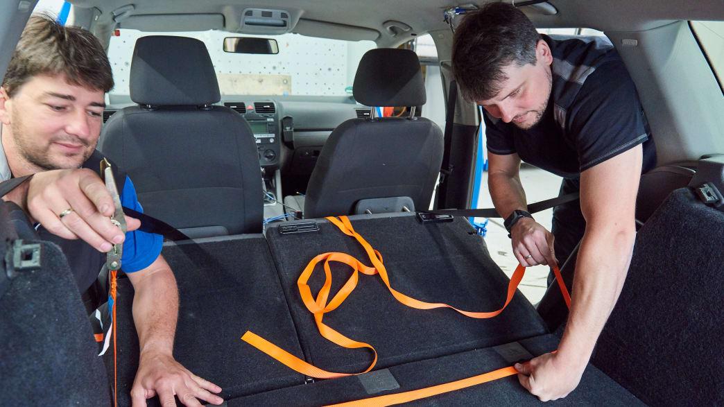 Mitarbeiter befestigen Spanngurte in Vorbereitung für den Crashtest Gepäcksicherung