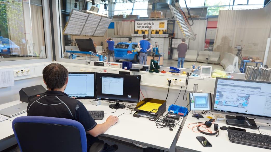 Blick über Computerbildschirme in die Crashhalle im Testzentrum in Landsberg. Vorbereitungen für den Crashtest Gepäcksicherung laufen.