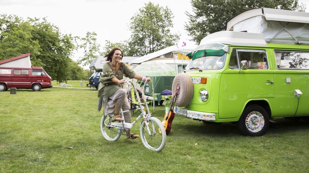Frau fährt auf einem Fahrrad auf dem Rasen