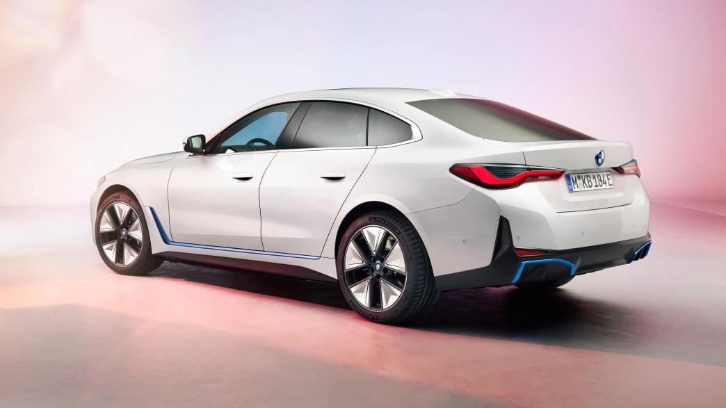 Heck und Seite eines neuen weißen BMW 4i im Studio auf buntem Pastellfarbenen Hintergrund und Boden