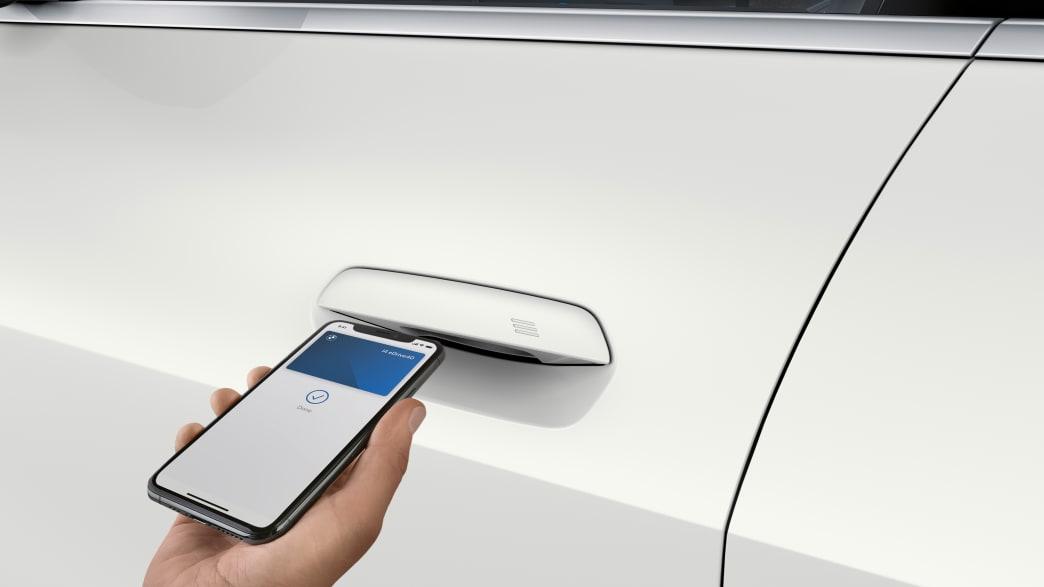 Person öffnet die Tür eines BMW i4 mit dem Handy