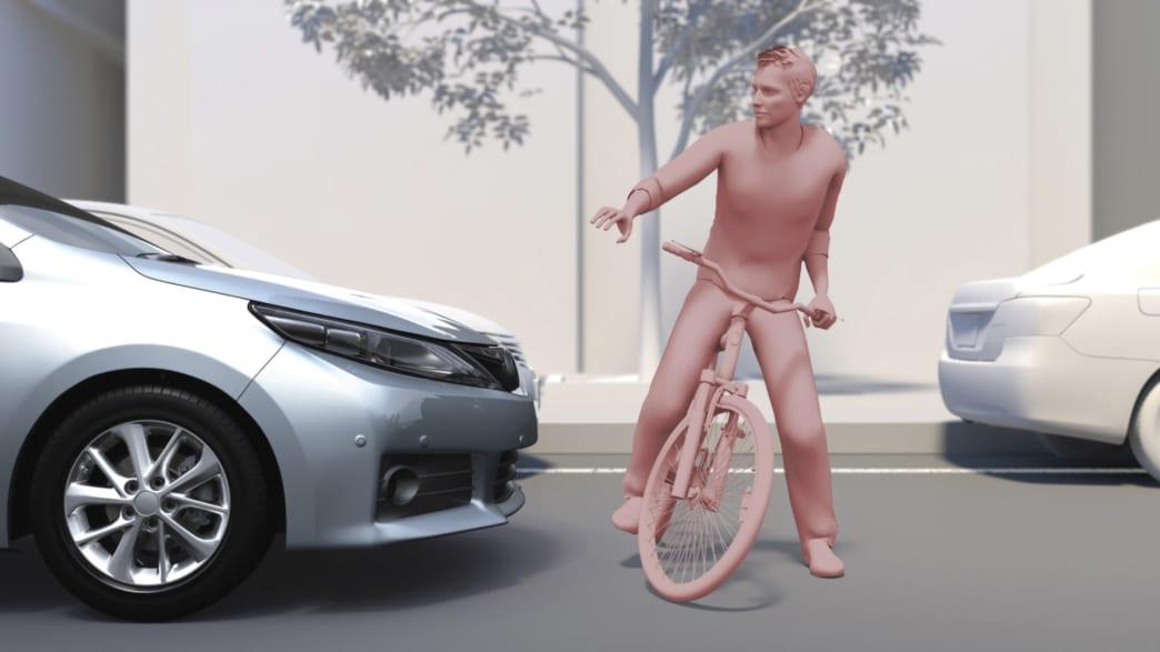 silberner Toyota RAV 4 bremst vor einem Fahrradfahrer