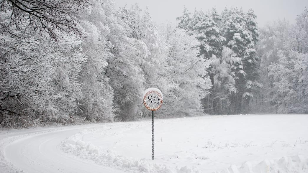 Schneebedeckte Landstraße mit verschneitem Verkehrsschild