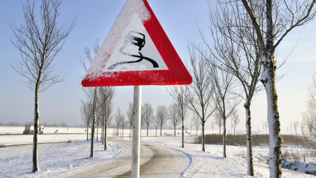 Verschneites Verkehrszeichen mit Hinweis auf verschmutzte Fahrbahn
