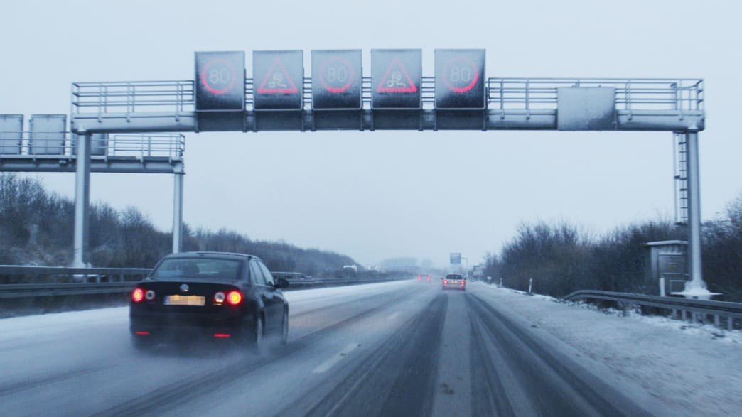 Auto fährt auf verschneiter Autobahn