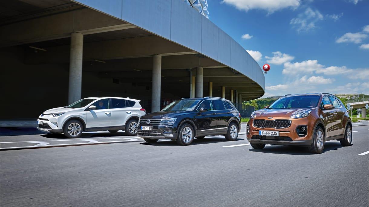 Drei SUV fahren nebeneinander auf einer Strasse an einem Gebaude vorbei