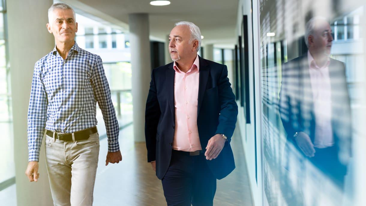 Zwei Männer gehen Gang entlang