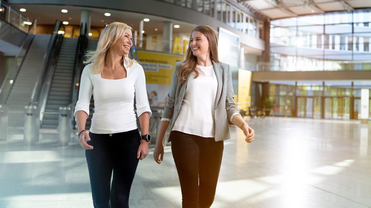 Zwei Frauen gehen durch Eingangshalle der ADAC Empfangshalle