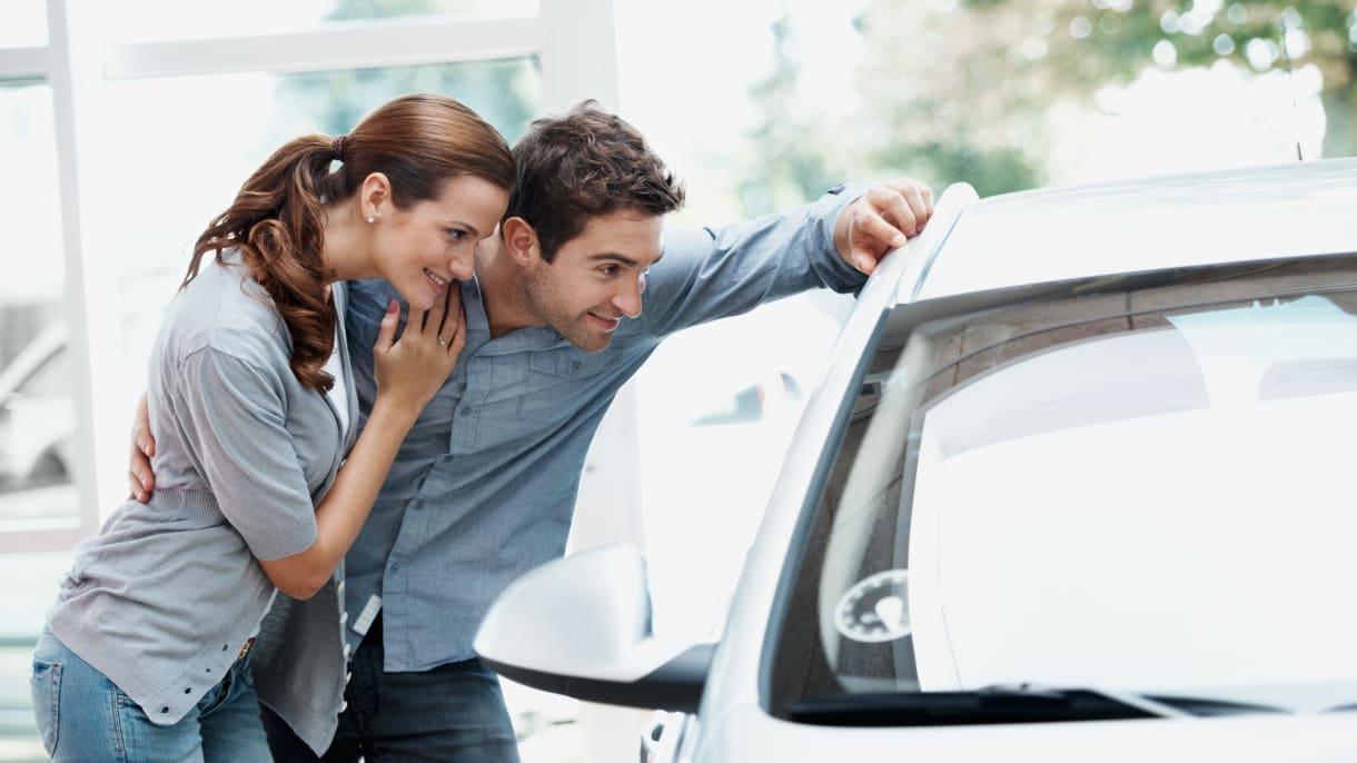 ein junges Paar beim Autokauf