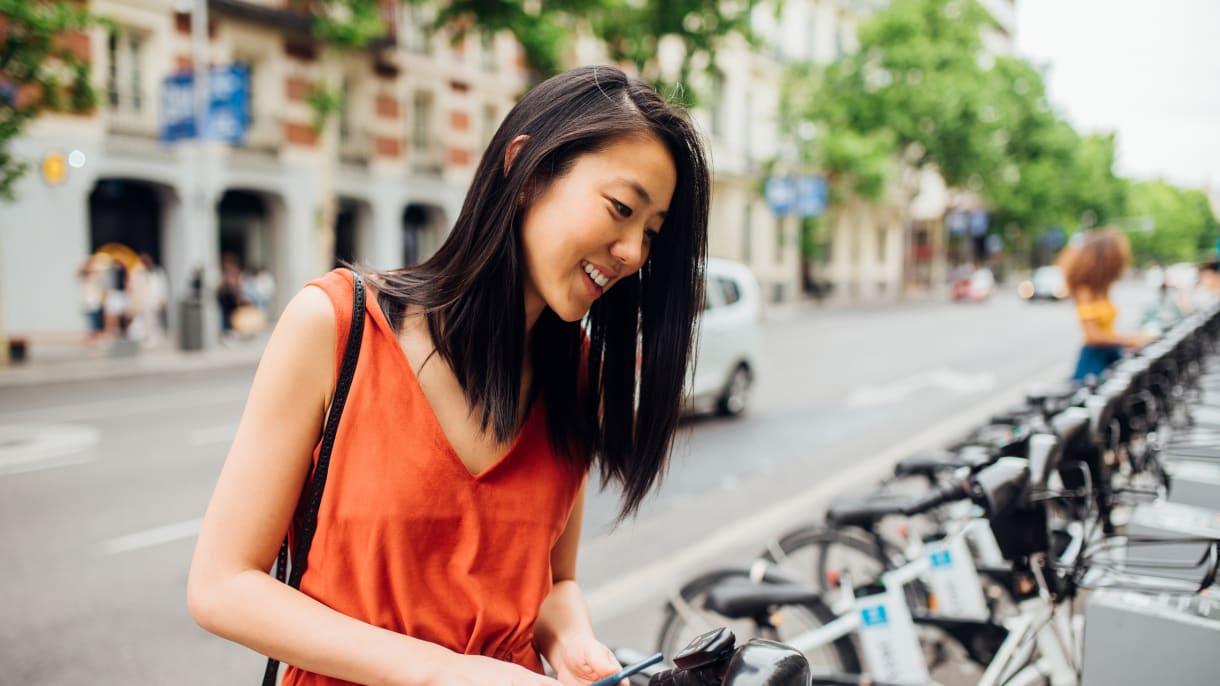Junge Frau leiht sich Bikesharing Rad aus