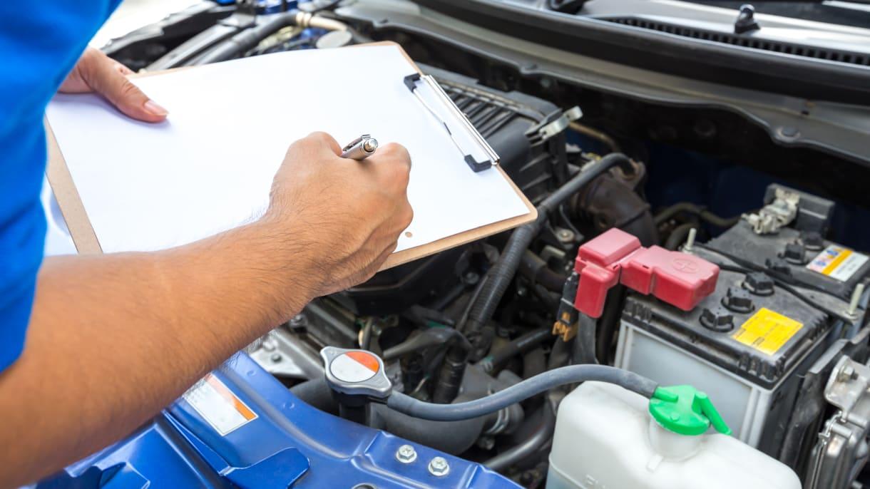 Ein Mechaniker untersucht ein Auto in einer Werkstatt