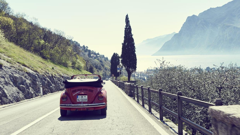 roter VW Käfer fährt am Gardasee entlang