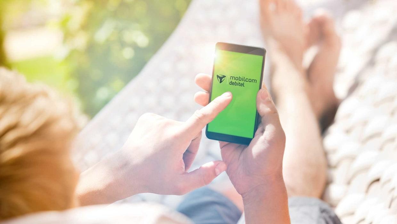 Frau liegt in der Hängematte und nutzt Mobilcom auf ihrem Smartphone