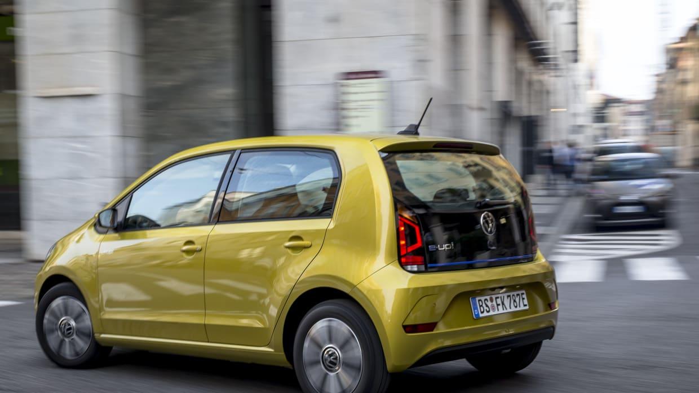 gelber VW e-Up fahrend von hinten