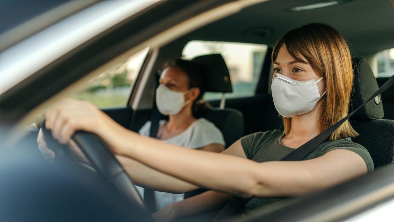 Zwei Frauen fahren mit Mund-Nasen-Schutz Auto