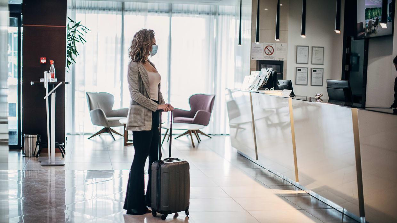 Frau mit Mundschutz steht mit einem Koffer in einer Hotellobby