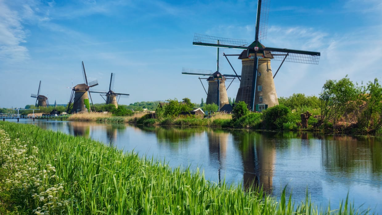 Windmühlen am Rande eines Flusses in Holland
