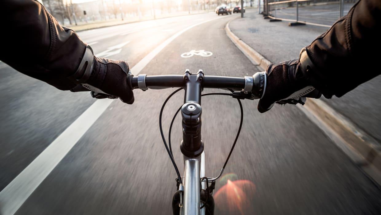 Blick über den Lenker eines fahrenden Fahrradfahrers nach vorne auf den Radweg