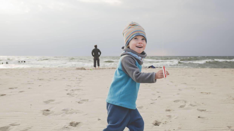 Junge lässt Drachen an Ostsee steigen