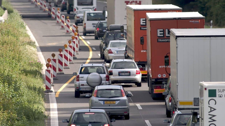 Autos wenden Reißverschlussverfahren in einer Baustelle an