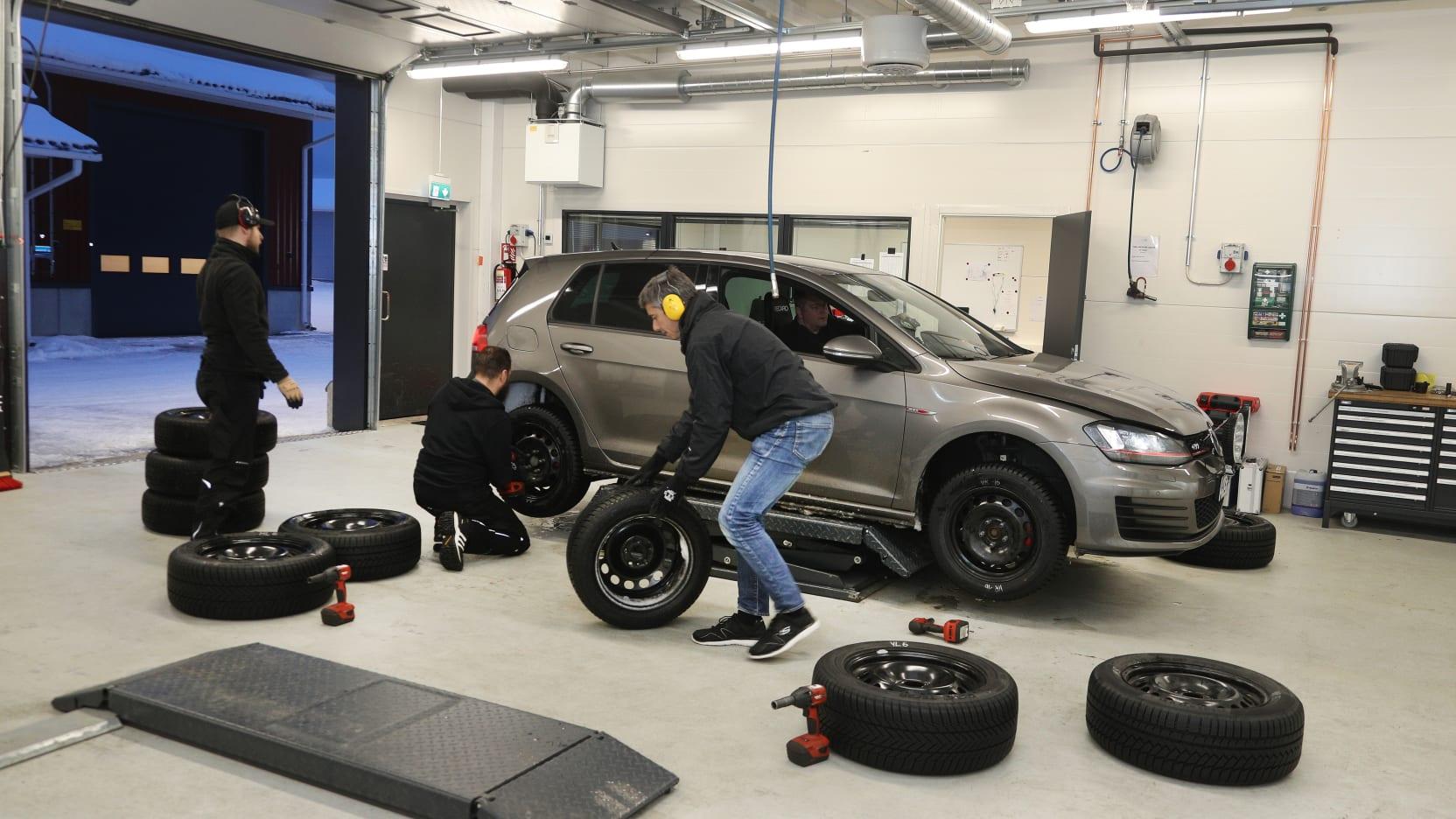 Männer wechseln bei einem Auto die Reifen