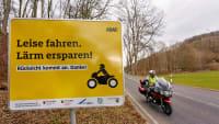 Ein Motorradfahrer fährt an einem Schild an der Landstrasse im Gelbachtal vorbei, das Biker um eine leise und rücksichtsvolle Fahrweise bittet. Vor dem Saisonstart startet der ADAC unterstützt vom Land Rheinland-Pfalz ein Pilotprojekt gegen Motorradlärm.