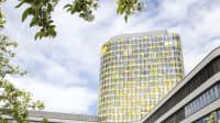 ADAC Zentrale Turm vor bayrischem weißblauem Himmel und blühendem Ast im Vordergrund