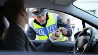 Polizist kontrolliert Fahrzeugschein eines Autofahrers