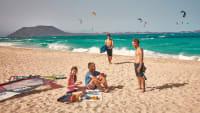 Freunde sitzen am Strand von Fuerteventura