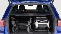 In einem Kofferraum wird ein Kinderwagen verstaut