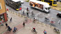 Belebte Kreuzung in Berlin mit Fussgängern, Radfahrern, Autos, Bus und Tram