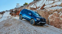 Blauer Dacia Duster fahert einen Hang hinunter