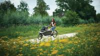 Frau fährt mit ihrem Kind auf einem E-Lastenrad