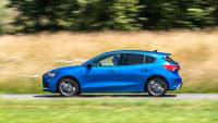 blauer Ford Focus faehrt durch Landschaft