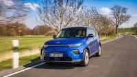 Blauer Kia E-Soul faehrt auf Strasse durch Landschaft