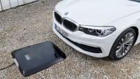 BMW fährt auf eine Ladeplatte zum induktiven Laden