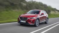 Der Mazda CX 3 Modelljahr 2021 fährt dynamisch auf einer Strasse.