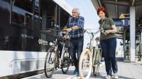 """Älteres Ehepaar bei der Fahrrad-Mitnahme in Sachsen-Anhalt vor einem Zug mit dem mit dem Kennzeichen """"Mein Takt"""""""