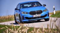 Ein blauer BMW 135i fährt auf einer Landstraße im Sommer