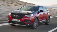 Opel Grandland X Hybrid fährt dynamisch auf einer Strasse