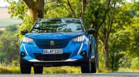 ein blauer Peugeot fährt auf einer Strasse
