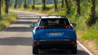 ein blauer Peugeot fährt auf einer Strasse, zu sehen ist der Wagen von hinten.